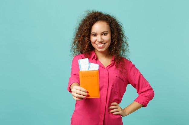 핑크색 캐주얼 옷을 입은 웃고 있는 아프리카 소녀, 여권을 들고 스튜디오의 파란색 청록색 벽 배경에 격리된 탑승권. 사람들은 진심 어린 감정 라이프 스타일 개념입니다. 복사 공간을 비웃습니다.
