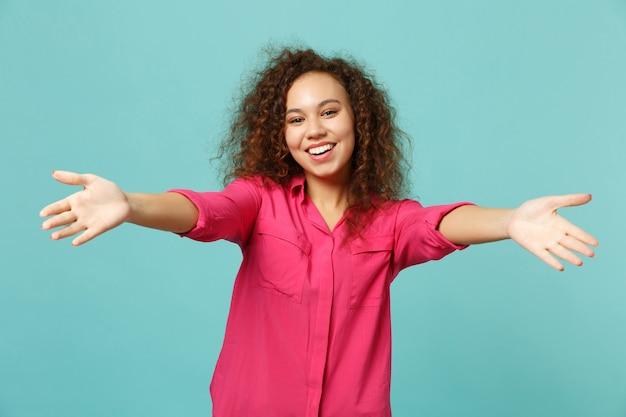 スタジオで青いターコイズブルーの背景に分離された抱擁のために伸ばした手で立っているピンクのカジュアルな服を着て笑顔のアフリカの女の子。人々の誠実な感情、ライフスタイルのコンセプト。コピースペースをモックアップします。