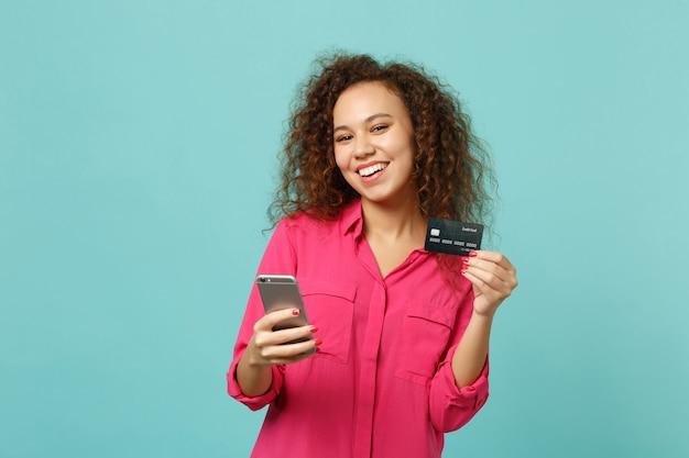 스튜디오에서 파란색 청록색 배경에 격리된 신용 은행 카드를 들고 휴대전화를 사용하여 분홍색 캐주얼 옷을 입은 웃고 있는 아프리카 소녀. 사람들은 진심 어린 감정 라이프 스타일 개념입니다. 복사 공간을 비웃습니다.