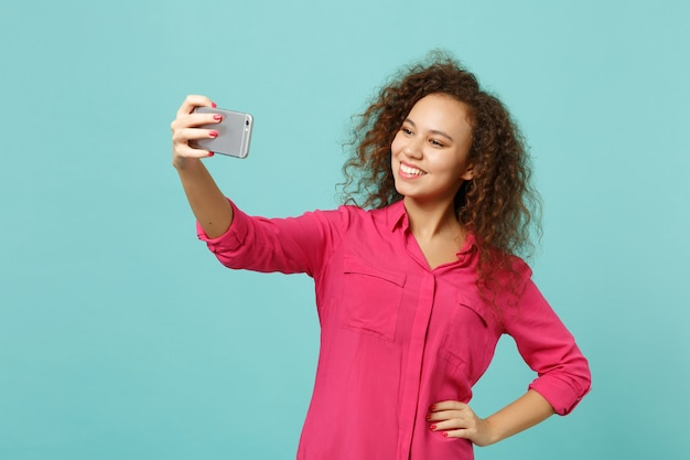 Smiling african girl in pink casual clothes doing selfie shot on mobile phone isolated on blue turquoise wall background in studio. people sincere emotions, lifestyle concept. mock up copy space.
