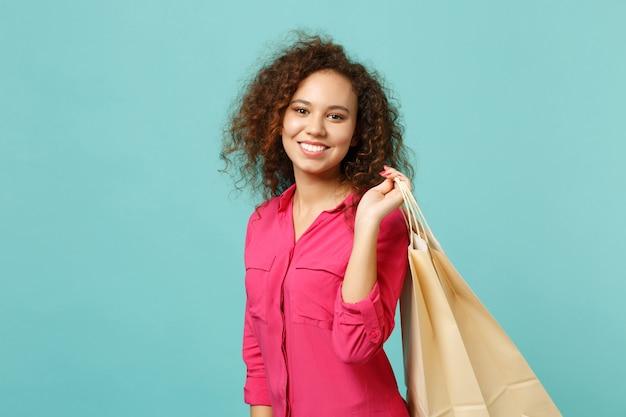 Sorridente ragazza africana in abiti casual rosa che tengono la borsa del pacchetto con gli acquisti dopo lo shopping isolato su sfondo blu turchese parete. concetto di stile di vita di emozioni sincere della gente. mock up copia spazio.