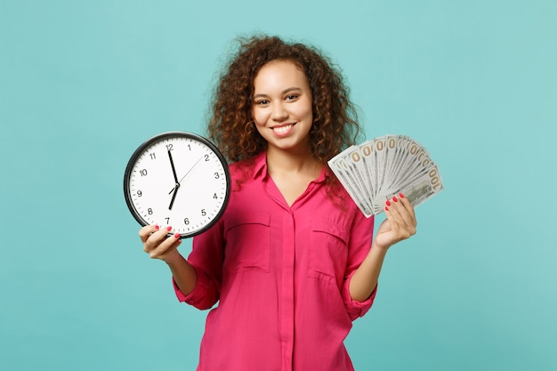 Smiling african girl in pink clothes hold round clock fan of money in dollar banknotes cash money isolated on blue turquoise background. people sincere emotions, lifestyle concept. mock up copy space.