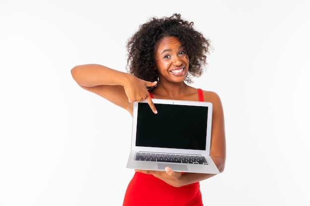Smiling african girl shows laptop screen with mockup on white background