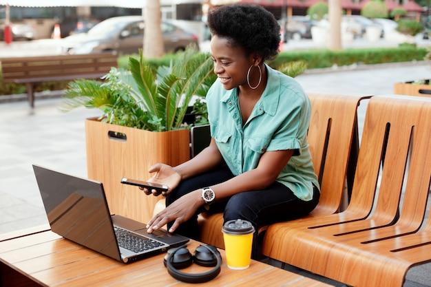 Улыбающаяся африканская девушка сидит в уличном кафе и работает за компьютером. девушка проверяет данные на ноутбуке и в телефоне. работа в сети, бизнес в сети.