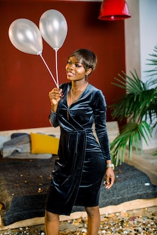 Smiling african girl with balloons in a dark dress standing in cozy room. birthday, new year, women's day concept
