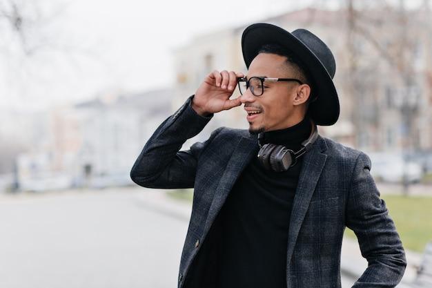 彼の眼鏡に触れて周りを見回しているウールのジャケットを着たアフリカ人の笑顔。屋外で天気の良い日を楽しんでいる茶色の肌を持つ幸せな若い男。