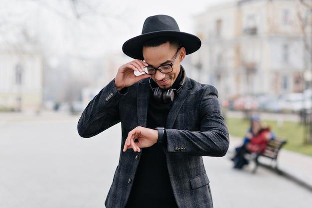 通りに立っている間腕時計を見ているアフリカ人の笑顔。公園でガールフレンドを待っている幸せな若い男の屋外の肖像画。
