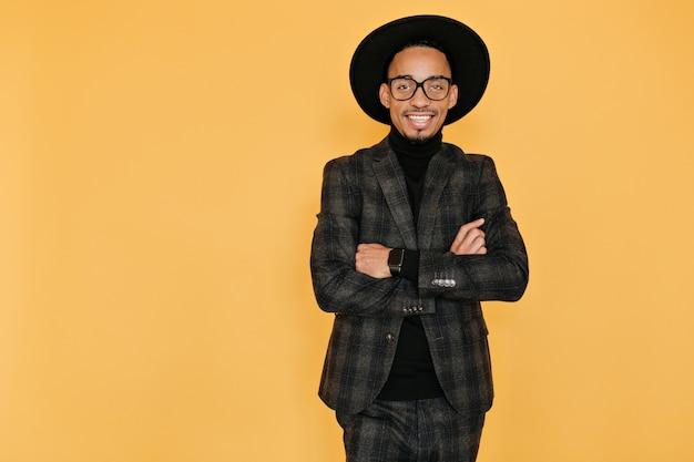 インスピレーションを得た表情で笑顔のアフリカ人。黄色の壁に腕を組んで立っている帽子をかぶった喜んでいる黒人男性の屋内写真。
