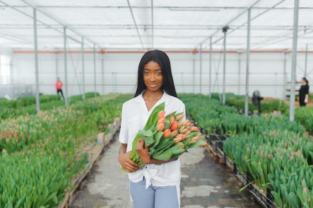 Улыбающийся африканец держит букет тюльпанов на плантации в теплице