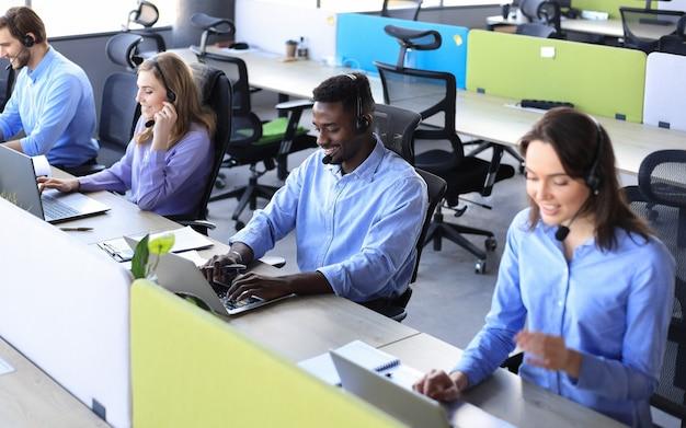Улыбающийся африканский мужчина-оператор call-центра с наушниками сидит в современном офисе с коллегами на заднем плане, консультируя онлайн.