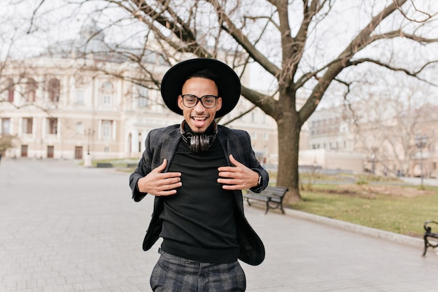 Smiling african man in checkered pants posing at square. outdoor photo of glad mulatto boy in hat and headphones chilling on street.