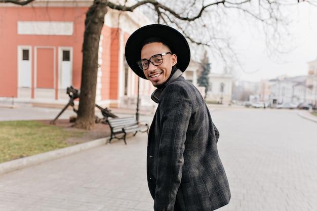 笑顔でベンチに行くアフリカ人の笑顔。肩越しに見て笑っている魅惑的な黒人男性の屋外の肖像画。