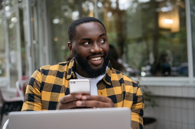 Smiling african man holding smartphone, working online. portrait of young successful developer planning start up, sitting at workplace.