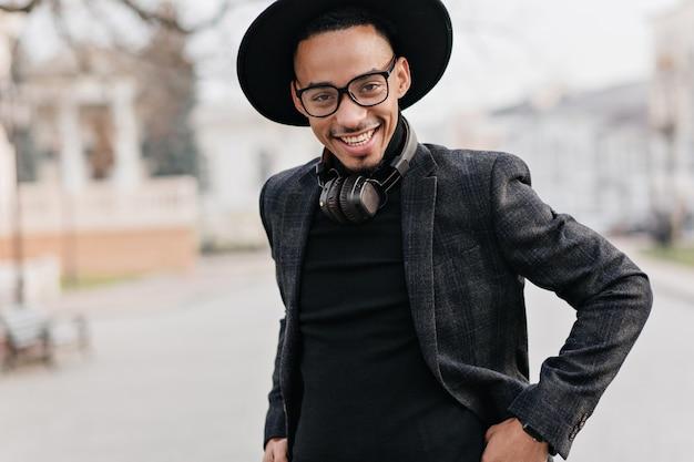 黒のセーターのポーズで笑顔のアフリカ人。街で週末を楽しんでいるカジュアルな服装の壮大な男。