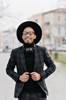 자신감이 포즈 서 안경에 웃는 아프리카 남자. 잘 생긴 남자의 야외 초상화는 세련된 체크 무늬 양복을 입고 행복을 표현합니다.