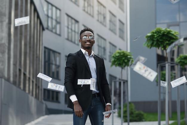 スーツを着た笑顔のアフリカ人がカメラにお金を投げる