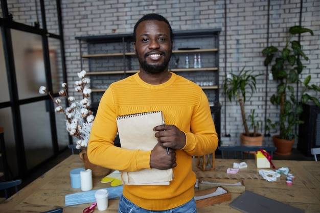 Smiling african man posing in art and craft studio
