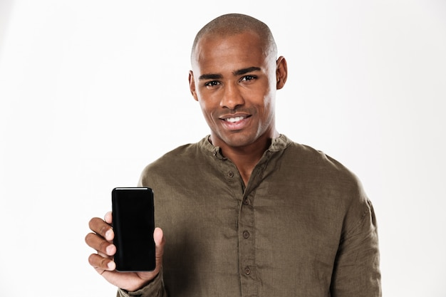 Smiling african man showing blank smartphone screen and looking