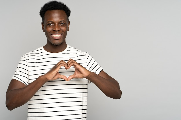Smiling african man showing heart sign with fingers, feels grateful for love, thankful and support.