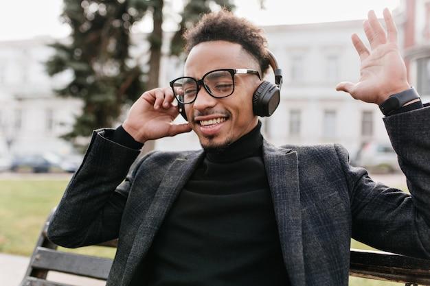벤치에 앉아 긍정적 인 감정을 표현하는 웃는 아프리카 남자. 아침에 헤드폰에서 흑인 남자 듣는 음악을 웃 고있다.