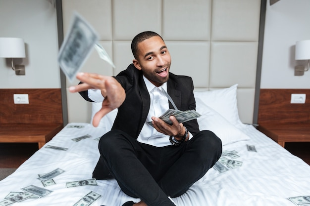 Smiling african man in suit throws the money at camera and sitting on bed in hotel room