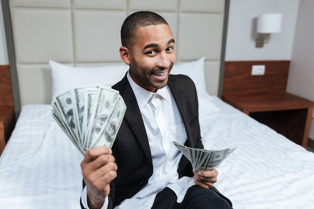 Smiling african man in suit with money in hands sitting on bed in hotel room and looking at camera
