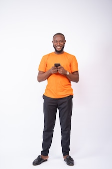 Smiling african man texting on his phone standing on a white background