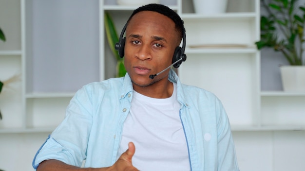 Smiling african professional call center operator wear wireless headset afro american businessman customer technical customer support service