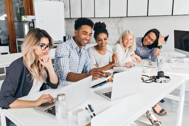 노트북 화면에서 연필로 가리키는 웃는 아프리카 학생. 사무실에서 컴퓨터로 작업하는 동안 손으로 턱을지지하는 안경에 금발 여자를 집중.