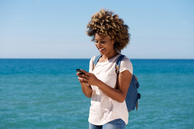 Smiling african woman on the beach reading text message on smart phone