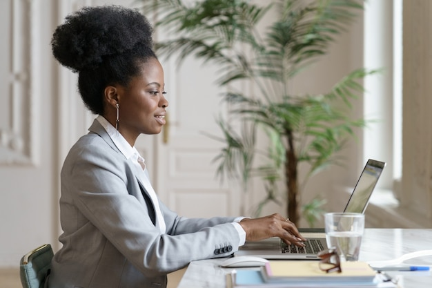 Smiling african woman in blazer sitting on desk, remote working at laptop at home office, studying