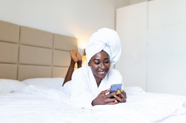 携帯電話でベッドに横になっているバスローブでアフリカの女性を笑顔、テキストメッセージ、ベッドの上に座っている間笑顔。