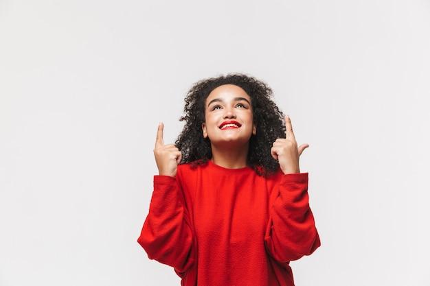 Улыбающаяся африканская женщина в красном свитере указывает и смотрит вверх на сером фоне