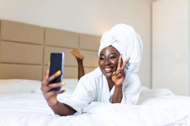 Selfieを取って携帯電話でバスローブのベッドに横になっている笑顔のアフリカの女性。ピースサインを見せて