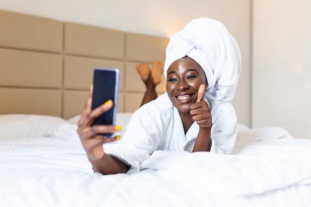 Selfieを取って携帯電話でバスローブのベッドに横になっている笑顔のアフリカの女性。親指を立てる