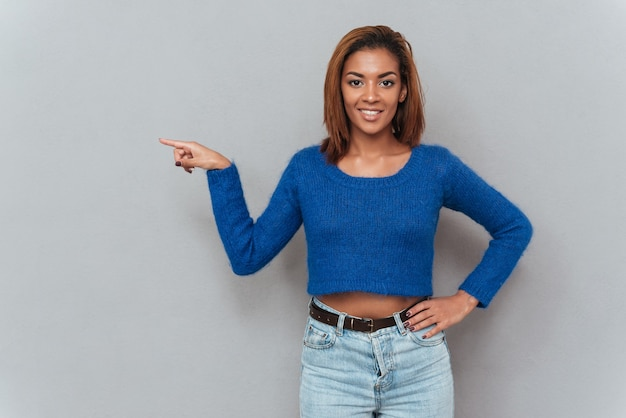 Smiling african woman in sweater showing finger away and holding second hand at hip.