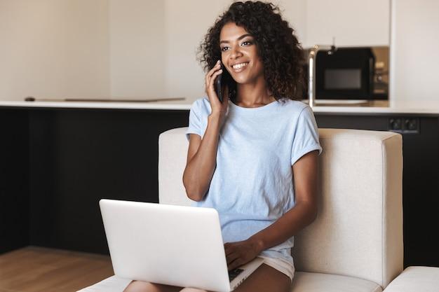 Улыбающаяся африканская женщина разговаривает по мобильному телефону