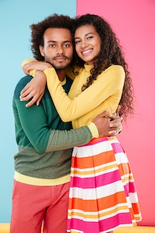 立って抱き締めて笑顔のアフリカの若いカップル