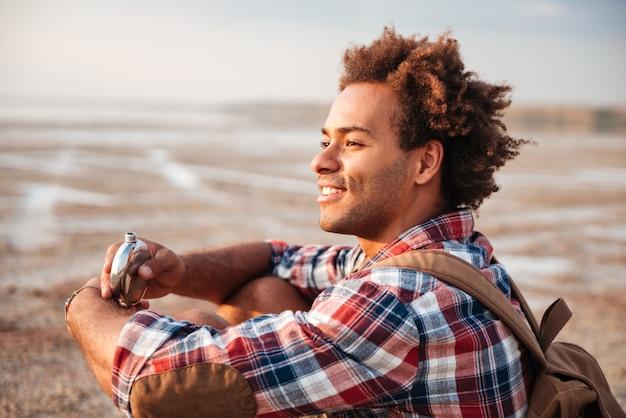 해변에 있는 힙 플라스크에서 배낭을 메고 웃고 있는 아프리카 청년