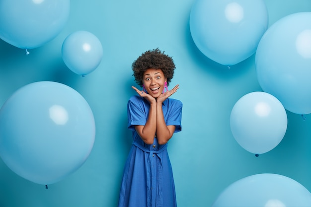 Smiling afro american girl spreads palms over face, enjoys awesome summer party, poses over inflated balloons in long blue fashionable dress, being in happy mood. celebration and lifestyle concept