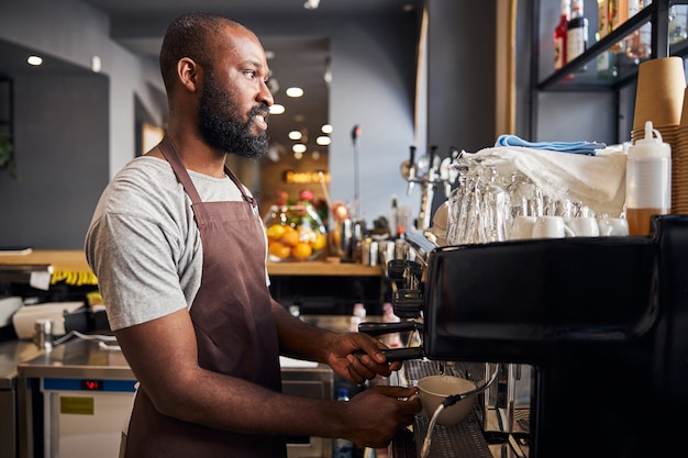 Smiling afro american man in apron holding white cup under tap of coffee machine while making espresso