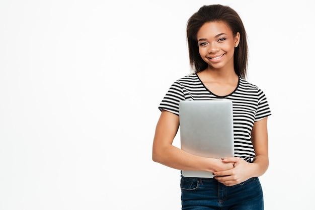 ラップトップを保持していると見ているアフロアメリカンの女性の笑顔