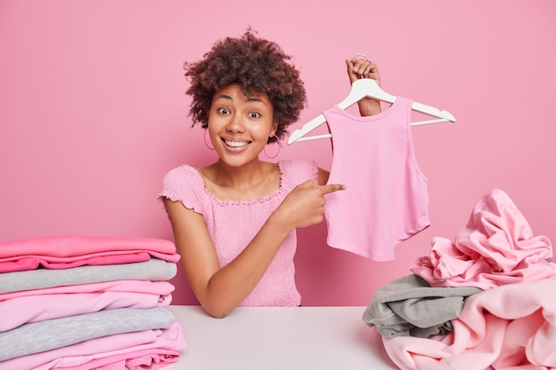 Smiling afro american woman points at her t shirt on hanger sorts out clothing for donation surrounded by pile of unfolded laundry stack of neatly folded clothes poses indoor against pink wall