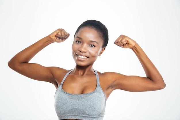 Улыбающаяся афроамериканская женщина показывает ее бицепс, изолированные на белом фоне
