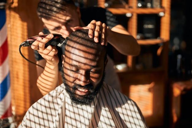 理髪店で散髪を取得している笑顔のアフリカ系アメリカ人の若い男
