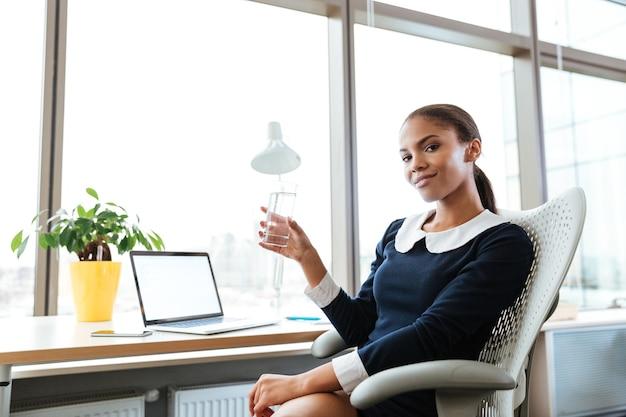 水のカップを手に、窓の近くのテーブルのそばに座って、オフィスでカメラを見てドレスを着て笑顔のアフロビジネス女性