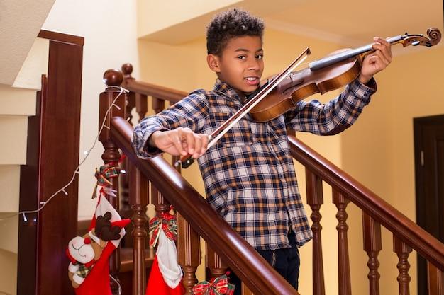 Улыбающийся афро-ребенок играет на скрипке мальчик играет на скрипке на рождество молодые скрипачи улыбаются, настоящее рождество ...
