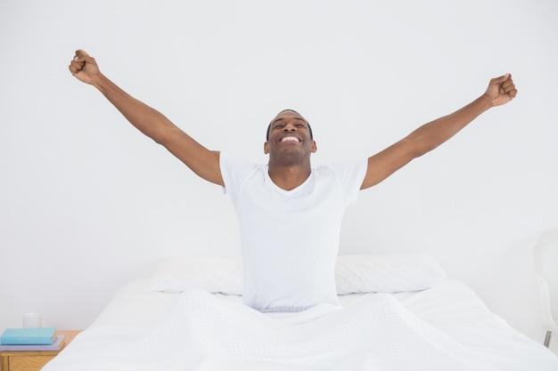 Улыбающийся человек афро, вытянув руки в постели
