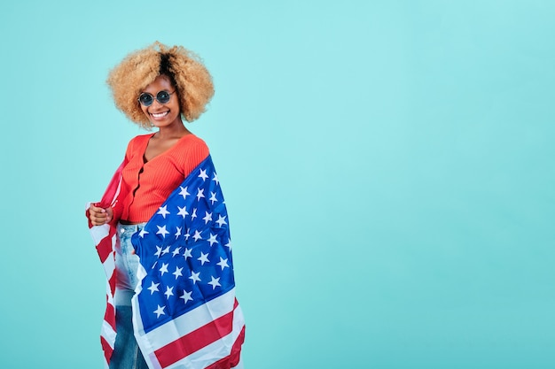 Smiling afro woman holding an usa flag while standing on an isolated background. usa independence day and patriotism concept.