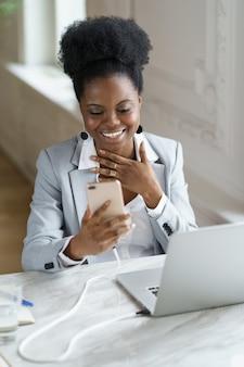 笑顔のアフロの女性がオフィスに座っているソーシャルメディアで週末について友人とチャットする休憩を取る